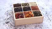 ceylon : Various kind of dry tea - green, black, red, fruit and blue in wooden box on the table. Top view. Tea time concept.