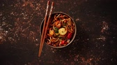 udon : Traditional asian udon stir-fry noodles with shrimp in bowl and chopsticks. Fresh chilli pepers on side. Placed on dark rusty background with copy space.