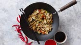 rice pan : Delicious fried rice with chicken. Prepared and served in a wok with soy and sweet sour souces on side. Placed on stone background. Top view. Stock Footage
