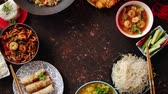 udon : Asian food set. Noodles, fried rice with chicken, tom yum soup, spring rolls, deep fried fish and udon with prawns. Top view on dark rustic background. Oriental style food circle composition.