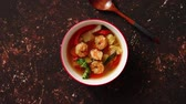 kaffir lime leaves : Traditional Tom Yum spicy Thai soup with shrimp, seafood, coconut milk and chili pepper in served red bowl. Fresh chilli pepper and wooden spoon on sides. Top view with copy space.