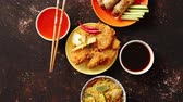 red cabbage : Spicy Thai deep fried fish coated in breadcrumbs and meat spring rolls Served with soy and hot sauces. Top view. Stock Footage