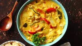 çili : Traditional Chinese or Thai chicken yellow curry with vegetables served with steamed rice cucomber and hot chilli pepper on side. Top view with copy space on dark rusty background.