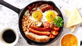 confiture : English breakfast in iron cooking pan with fried eggs, sausages, bacon, beaked beans, toasts, orange juice and black coffee on stone background.