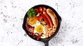 confiture : English breakfast in iron cooking pan with fried eggs, sausages, bacon, beaked beans, toasts on stone background.