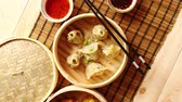 soma : Oriental traditional chinese dumplings served in the wooden steamer placed on bamboo mat. Top View composition.