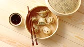 soma : Traditional chinese dumplings served in the wooden bamboo steamer over raw wooden background table. Top View composition. Stock Footage