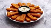 rántott : Crumbed fish sticks served with garlic dip sauce on a white plate on a stone table. Top view with copy space.