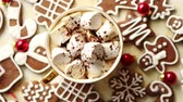 marshmellow : Cup of hot chocolate with tasety marshmellows. Fresh baked Christmas shaped gingerbread cookies on sides. With Xmas decorations. View from above.