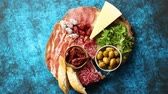 frankfurters : Delicious mix of different snacks and appetizers. Spanish tapas or italian antipasti on a wooden plate. View from above. Placed on blue table. Stock Footage