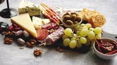 board : Antipasto platter cold meat and cheese board with grapes, wine, various kinds of cheese, grissini bread sticks on white rustic background. View from above