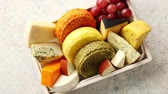 different cheeses : Fresh and delicious different kinds of cheeses placed in wooden crate with grapes. View from above. Concrete background with copy space. Stock Footage
