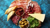 sausage slice : Delicious mix of different snacks and appetizers. Spanish tapas or italian antipasti on a wooden plate. View from above. Placed on blue table. Stock Footage