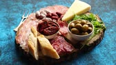 farklı : Delicious mix of different snacks and appetizers. Spanish tapas or italian antipasti on a wooden plate. View from above. Placed on blue table. Stok Video