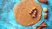 christmas recipes : Christmas baking concept. Gingerbread dough with different cutter shapes and spices on sides. Top view on blue rustic background. Stock Footage