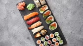 angolna : Fresh sushi rolls set with salmon and tuna fish served on black stone board. Top view of traditional japanese cuisine. Stock mozgókép