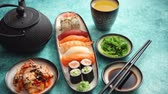 soja : Various sushi rolls placed on ceramic plates. Traditional iron tea pot and green tea in cup. Kimchi and goma wakame salads. Soy souce and chopsticks on sides. Blue background.