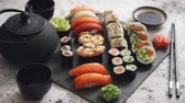 ardósia : Assortment of different kinds of sushi rolls placed on black stone board. Traditional asian iron tea pot on side. Top angle view.