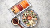 angolna : Asian food assortment. Various sushi rolls placed on ceramic oriental style plates. Soy souce and chopsticks on sides. Grungy dark background with copy space. Stock mozgókép