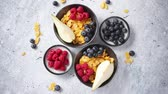flocos de milho : Healthy breakfast for two is served. Golden cornflakes with fresh fruits of raspberries, blueberries and pear in two ceramic bowls. Placed on stone background. Vídeos