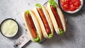 yellow dog : Three barbecue grilled hot dogs with sausage placed on wooden cutting board. Bowls with tomato and onionon sides. Traditional american fast food. Above angle view.