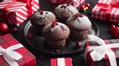 christmas recipes : Christmas chocolate delicious muffins served on black ceramic plate. Sprinkled with powder sugar. Cranberries on top. Xmas gifts and decorations on sides. Stock Footage