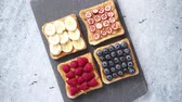 żurawina : Healthy breakfast toasts. Wholegrain bread slices with peanut butter and various fruits. Served on grey cutting board. Top view, grey stone background. Dieting concept Wideo