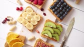 mantequilla de mani : Assortment of healthy fresh breakfast toasts. Bread slices with peanut butter and various fruits and ingredients on side. Placed on white wooden table. Top view, with copy space.