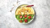 omelete : Classic egg omelette served with cherry tomato and arugula salad on side. Placed on white ceramic plate. Stone background with copy space. Vídeos