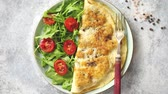 rúcula : Classic egg omelette served with cherry tomato and arugula salad on side. Placed on white ceramic plate. Stone background with copy space. Vídeos