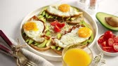abacate : Delicious healthy breakfast with sliced avocado sandwiches with fried egg on top of bread. With orange juice, cherry tomatoes, radish sprouts, salt and peper. Flat lay, top view. Stock Footage