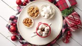 nogueira : Delicious homemade christmas hot chocolate or cocoa with marshmellows in a red xmas decorative cup. With almonds, walnuts in small bowls on side Stock Footage