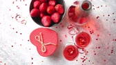 efervescente : Bottle of rose champagne, two glasses with fresh ripe strawberries and heart shaped boxed gift, placed on stone table for a special romantic occasion or Valentines. With copy space Stock Footage