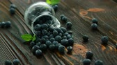 Closeup blueberry scattering from glass jug on dark wet wooden table