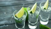 parcela : Row of glass shots with tequila and green sour lime slices on wooden table with heap of salt Stock Footage