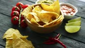 picante : Arranged bowl with crispy nacho chips and few bowls with served assortment of sauces on wooden table with chili pepper and lime
