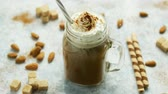 karmel : Glass jar with sweet caramel drink garnished with whipped cream and served with straw on table among nuts