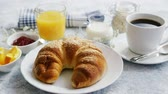 orange jelly : Served breakfast with baked golden croissant and jam with glass of orange juice on marble table