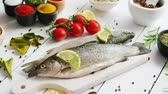 cutting fish : Various aromatic spices and bunch of fresh tomatoes lying on white wooden tabletop around cutting board with fresh trout