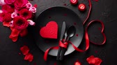 talheres : Valentines day, table setting and romantic dinner concept. Close up of plate with cutlery and rose petals on black stone background Stock Footage