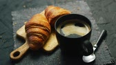 food : From above view of two fresh croissants and black mug with coffee placed on napkin on gray background of table