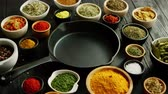 From above view of bowls with colorful spices and black pan placed in middle Vídeos