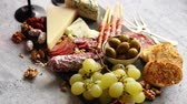 Antipasto platter cold meat and cheese board with grapes, wine, various kinds of cheese, grissini bread sticks on white rustic background. View from above