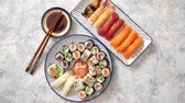 Asian food assortment. Various sushi rolls placed on ceramic oriental style plates. Soy souce and chopsticks on sides. Grungy dark background with copy space. Vídeos