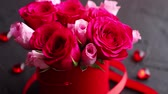luxurious : Pink roses bouquet packed in red box and placed on black stone background with copy space. Valentines day or Romantic concept. Stock Footage