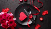 Valentines day, table setting and romantic dinner concept. Close up of plate with cutlery and rose petals on black stone background Vídeos