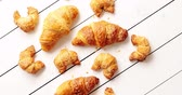 From above shot of set of yummy fresh croissants of assorted sizes lying on surface of white timber tabletop