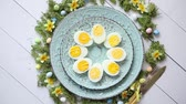 zastawa stołowa : Easter table setting with flowers and eggs. Decorative ceramic plates with boiled eggs halfs. Rustical dishware. View from above.