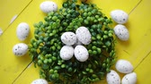 studentka : Green decorative Easter quail eggs wreath on yellow wooden table background. Top angle shot. Flat lay. Wideo