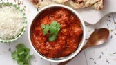 çili : Fresh and tasty Chicken tikka masala served in ceramic bowl. Indian spicy curry dish. With rice and naan bread on sides. Close up. Flat lay.